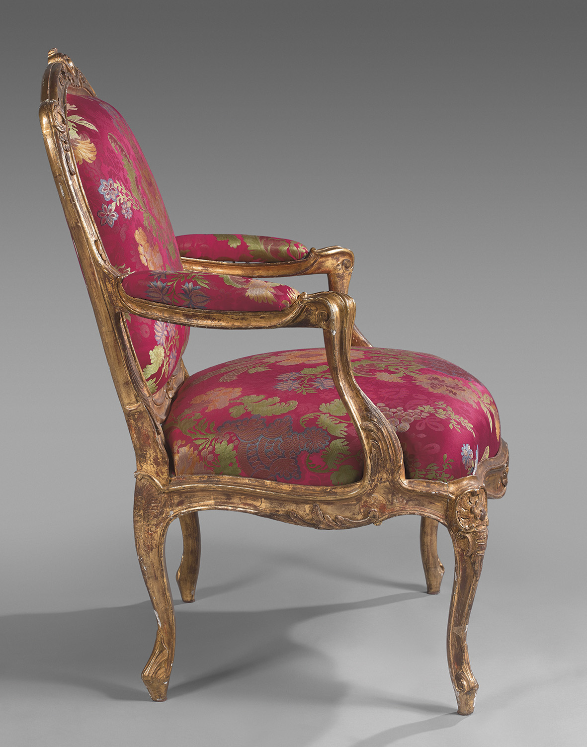 """This """"fauteuil à chassis"""" (removable frame armchair) in gilt beechwood carved with pomegranates and cartouches belongs to a set of six, tw"""