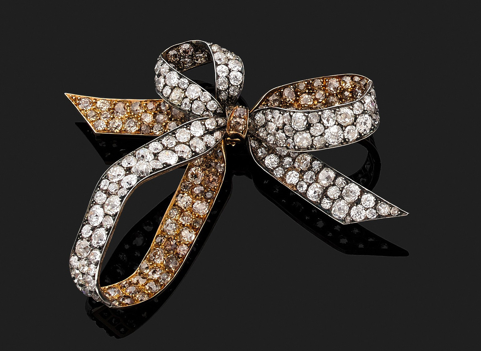 93750€René Lalique. Broche nœud à trois boucles en or 750millièmes et argent, pavée de diamants taille ancienne à épingle amovible, cir