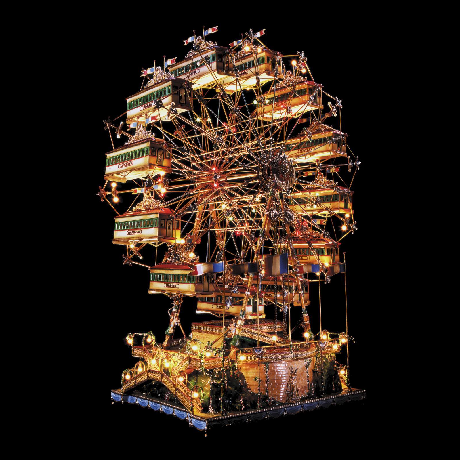 La grande roue des capitales(h. 88 cm), fabriquée en bronze,laiton et tôle d'acier par Jean-Pierre Hartmann en 1986, est éclairéede 130