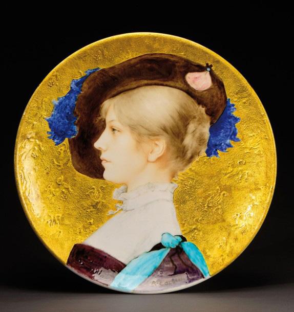 16575€ Théodore Deck et Raphaël Collin(1850-1916), plat circulaire en céramique émaillée polychrome figurant un profil de femme au chap