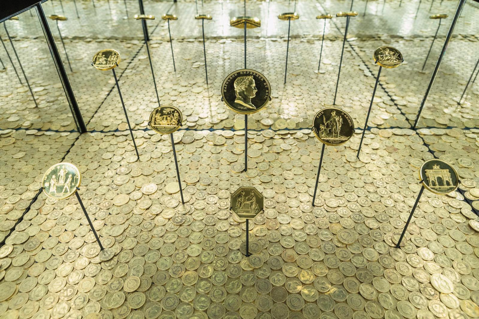 Médailles napoléoniennes présentées sur un tapis de 2 021 napoléons pour l'exposition à la Grande Halle de La Villette. Au premier plan, l
