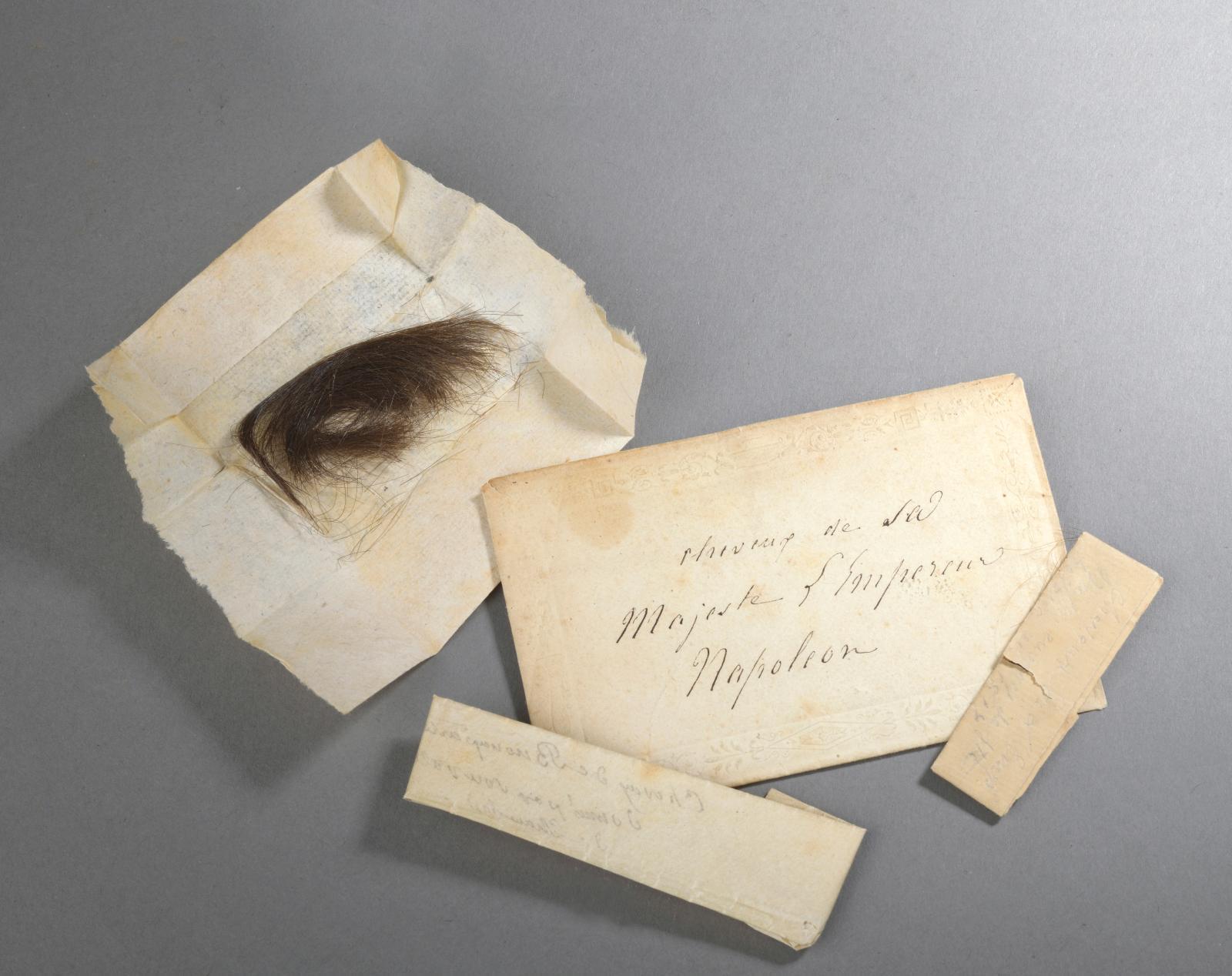 Petite enveloppe, à décor gaufré, manuscrite à l'encre sur le devant «Cheveux de Sa Majesté l'Empereur Napoléon», contenant trois plis, av