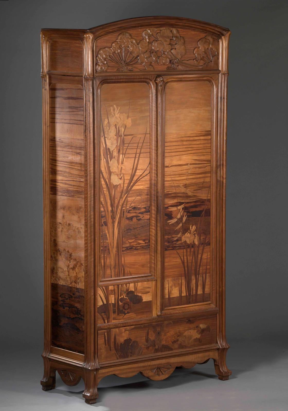 Armoire aux Ombellifères en noyer mouluré et sculpté et de bois précieux, marqueterie d'Iris des marais, de libellules et d'un papillon, fronton sculp