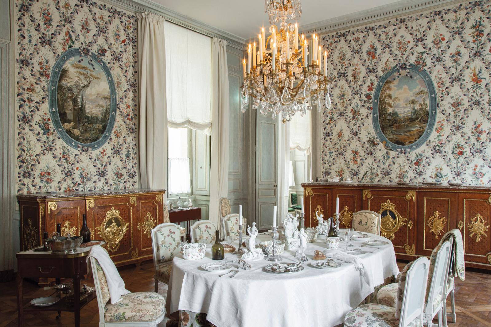 La table dressée évoqueLe Déjeuner d'huîtrespar Jean-François de Troy. Derrière, les deux meubles de Riesener, faits pour cette pièce, o