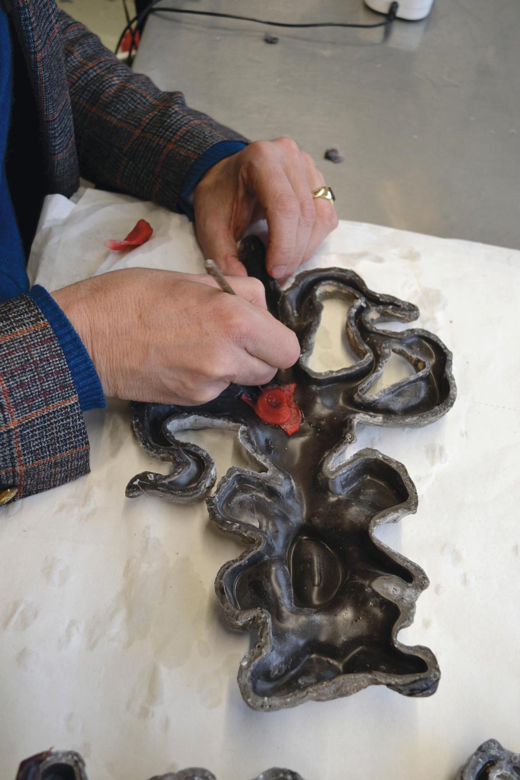 Johan Creten apposant sa signature sur une sculpture en cire: ses initiales et l'intaille de sa bague antique.