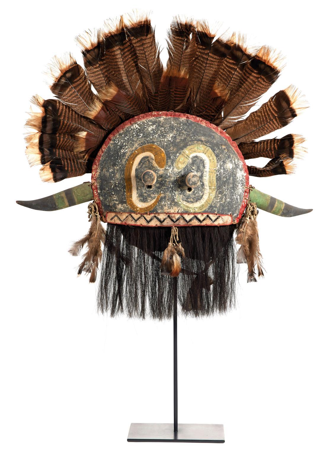 Ce masque à cornes semi-circulaire, aux yeux protubérants et surmonté d'une impressionnante coiffe de plumes et de barbes de crin de cheva