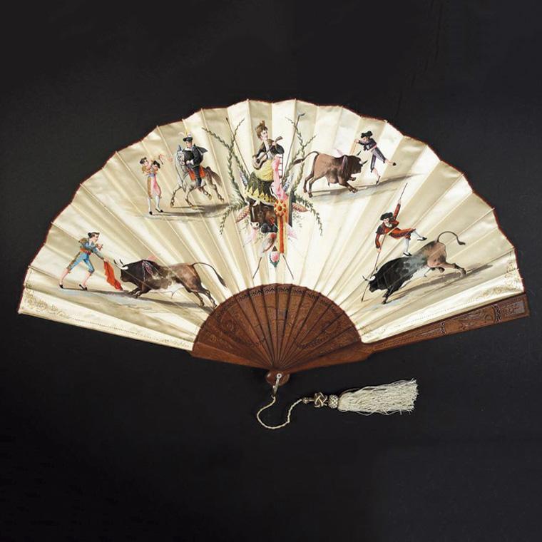 128€ Dans l'arène, vers 1890-1900, éventail plié, feuille en soie crème doublée rouge, monture en bois repercé et gravé sur le thème de l