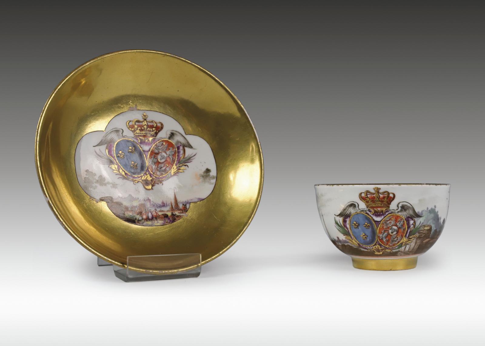 Meissen. Tasse-coupe avec sa soucoupe en porcelaine à décor polychrome de personnages, armes sur fond or de LouisXV et Marie Leszczynska,