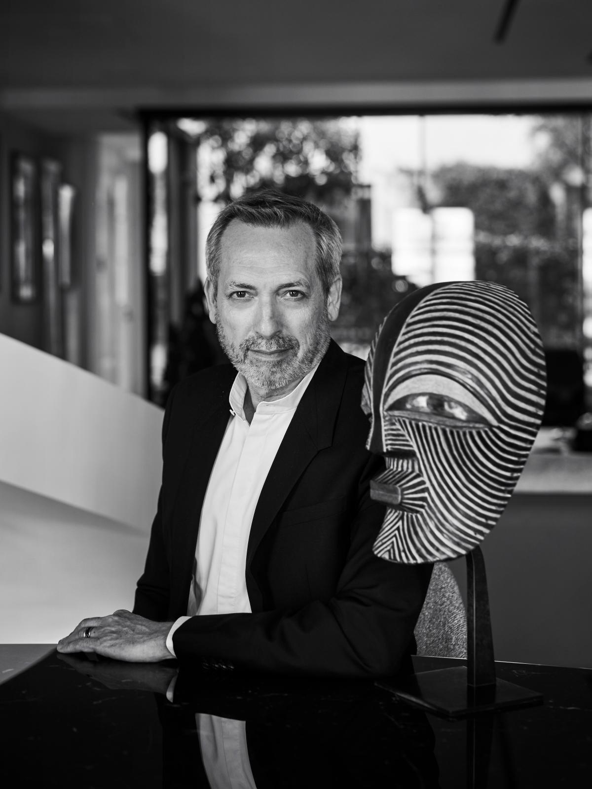 Guy Delcourt à côté du masque songye de sa collection. Photo Nicolas Guérin