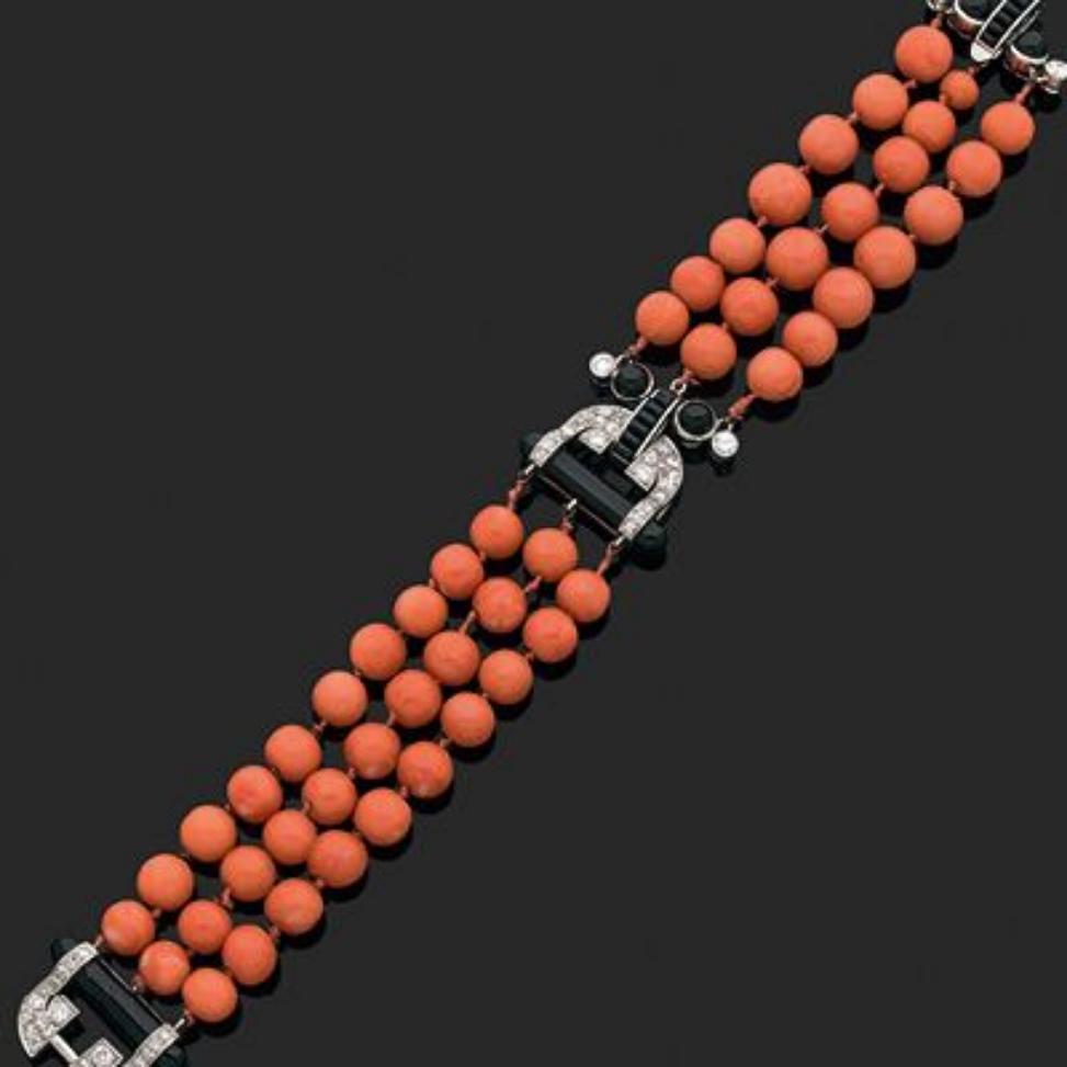 102000€ Cartier, vers 1920, bracelet en platine composé de trois rangs de perles de corail ornés de motifs «lyre» sertis de diamants e
