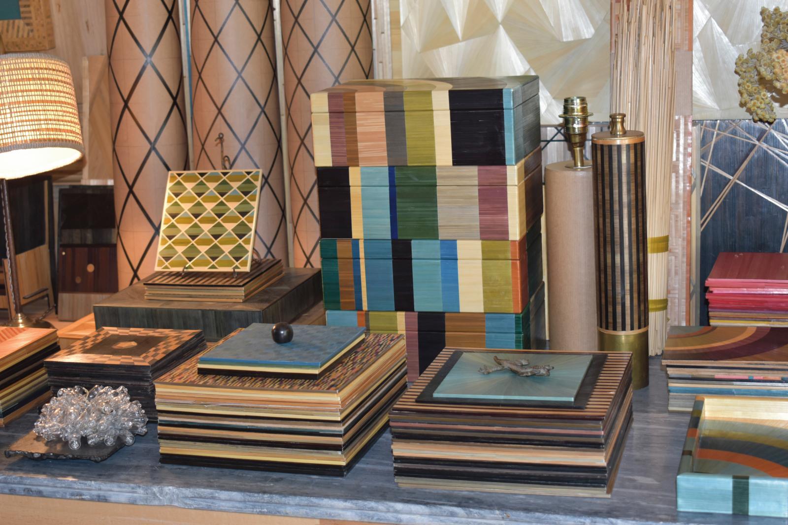 Échantillonnage de motifs et de couleurs combinant damiers, cylindres de losanges, polyèdres, jeux de rayures. À droite, pied de lampe ins