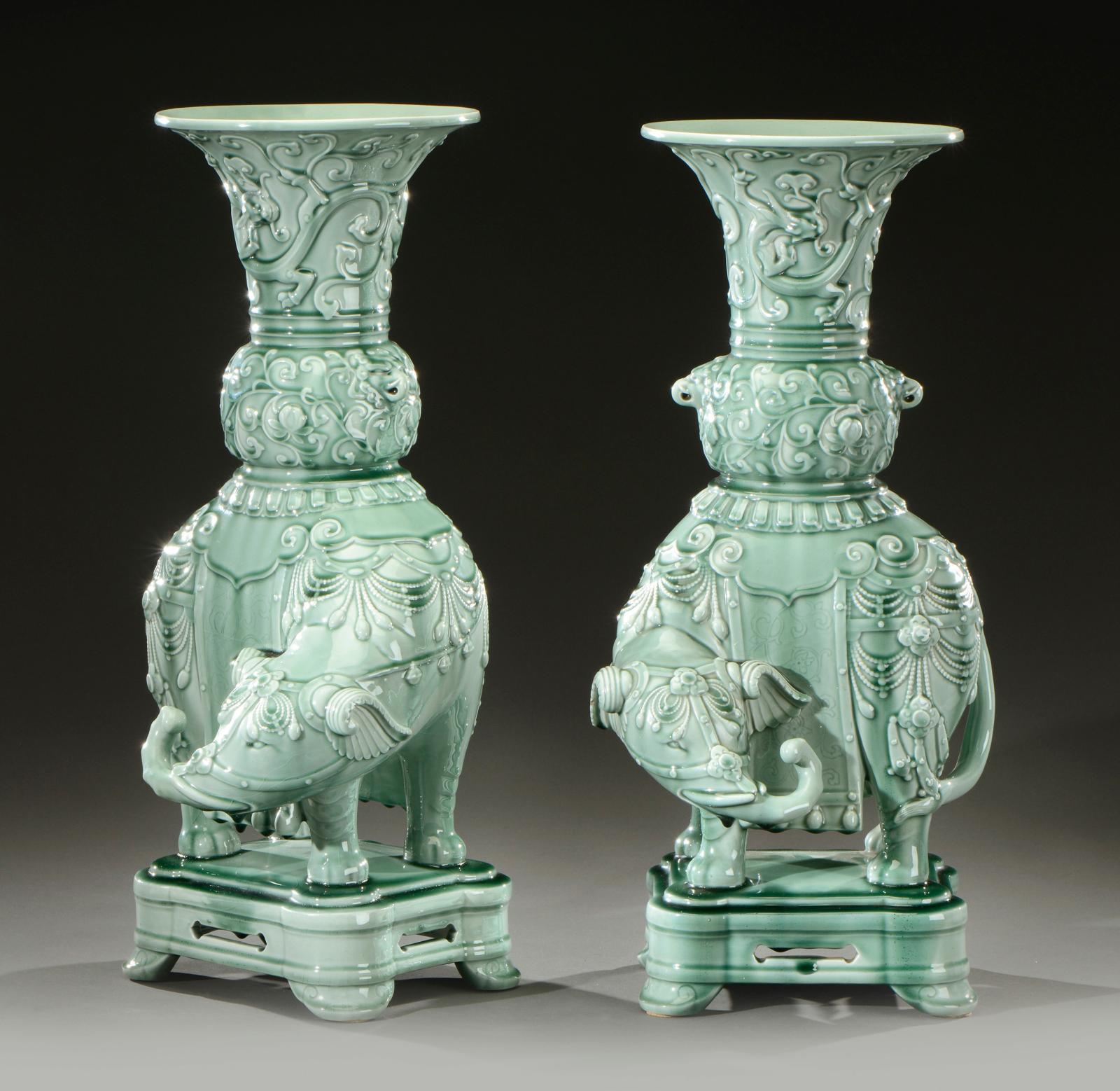 Théodore Deck, paire de vases en céramique émaillée vert céladon sur des éléphants, à un décor en léger relief de motifs floraux, d'éléphants et de dr